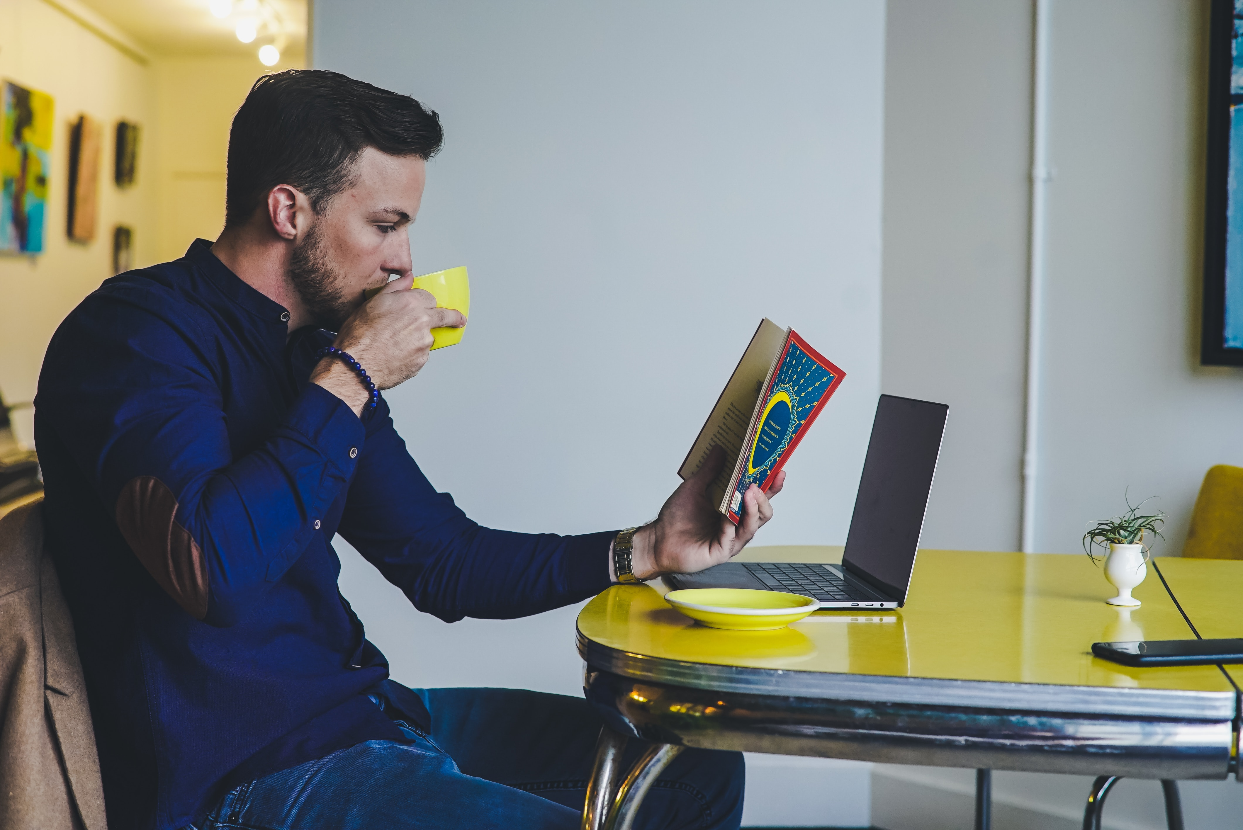 Man reading a book sipping coffee