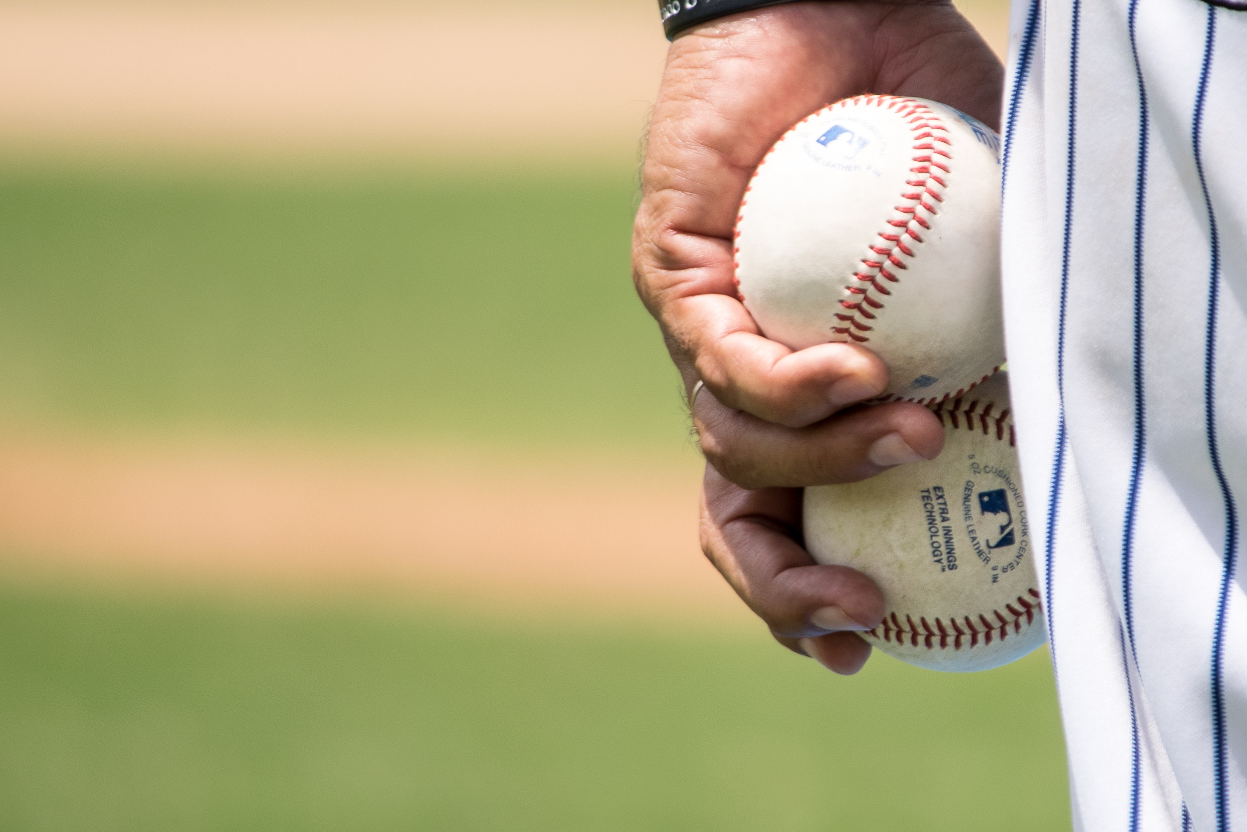 Person holding two baseballs. Photo by Jose Morales on Unsplash