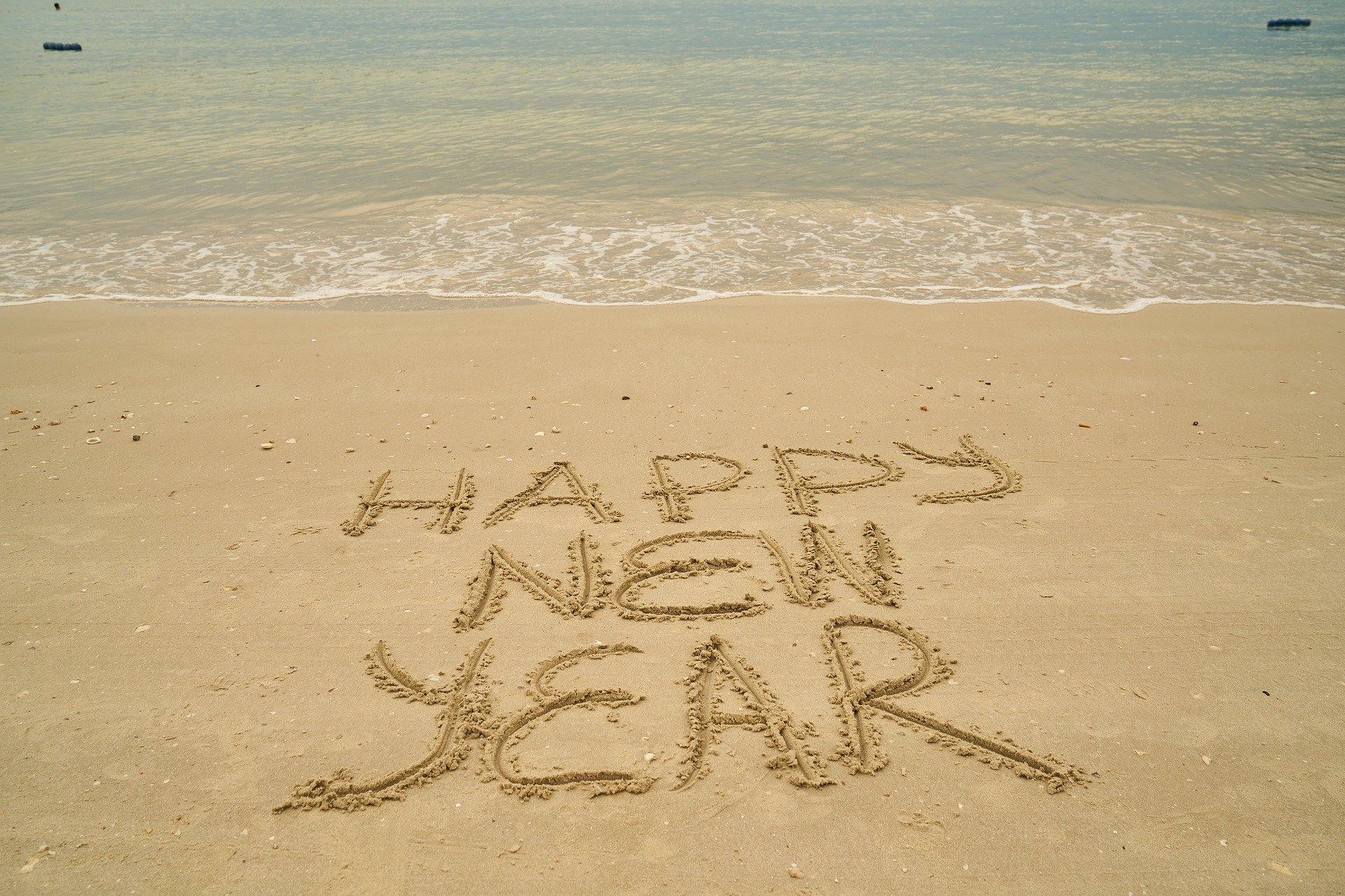 Happy New Year written in sand on the beach