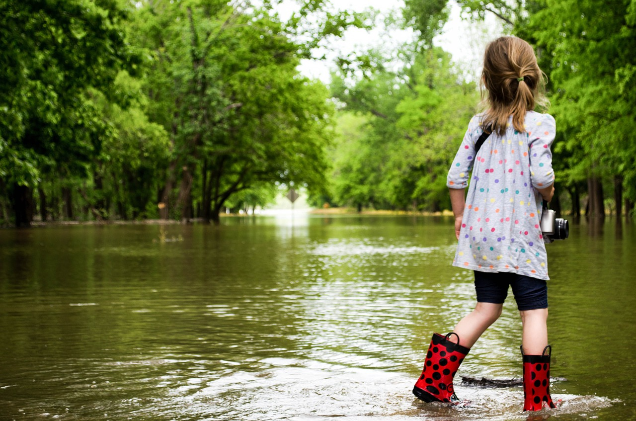 Girl in rain boots on flooded road