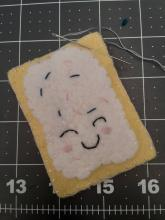 picture of small hand sewn breakfast pastry with sewing needle