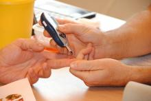 Close up of hands receiving help with a finger blood glucose test.